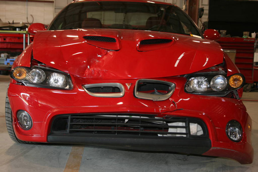 Red Pontiac GTO involved with front hood and bumper damage