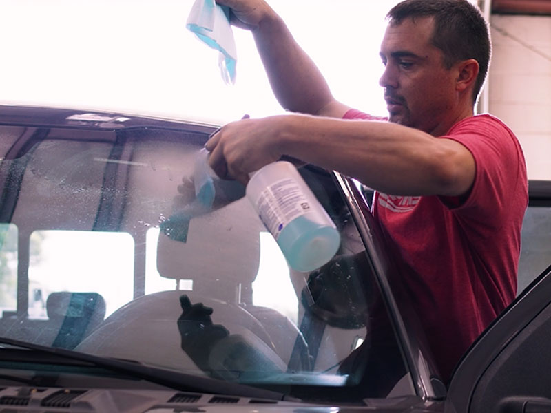 Final Finish employee cleaning car windshield