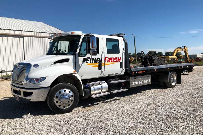 Final Finish White Flatbed Tow Truck on the job site