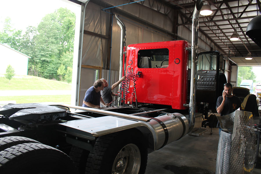 Mechanics working on red semi truck