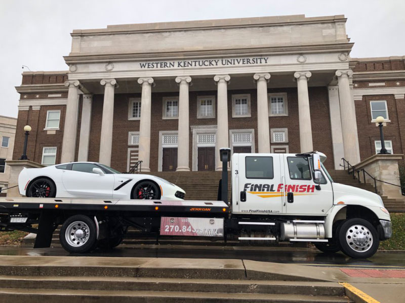 White corvette being towed by Final Finish's tow truck outside of WKU