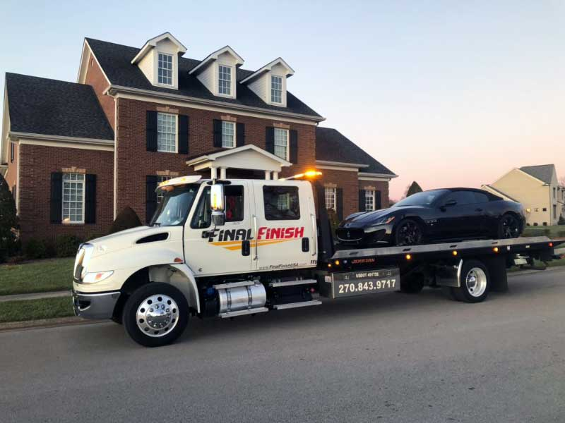 Black Maserati sports car being towed flatbed truck in a residential neighborhood