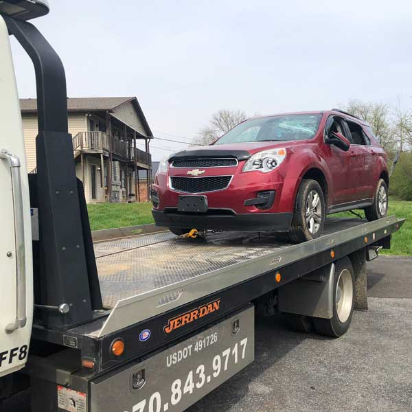 Red Chevrolet SUV on a flatbed tow truck